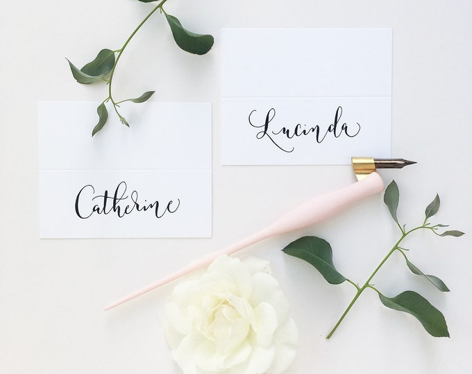Featured listing image: Simple white wedding place names with modern calligraphy in black ink / escort cards / place cards / personalised name cards for weddings