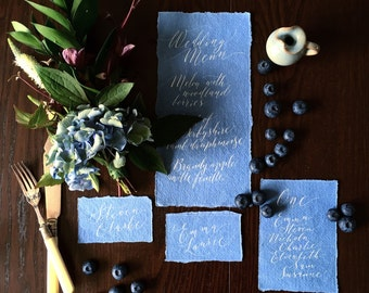 Whimsical dusky blue calligraphy wedding menus in white ink on luxe torn edge paper
