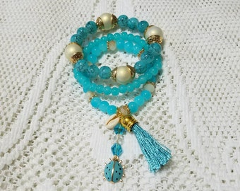 Set of Three Stackable Blue Beaded Bracelets with Sea Shell,Lady Bug Charm and Blue Tassel