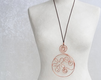 A large round copper pendant necklace, a wire wrapped handmade jewel, with shapes of spirals and flower, a unique piece of copper jewelry