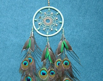 Dream catcher in light green and gold with feathers from the peacock
