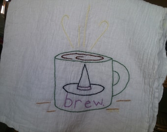 Hand embroidered tea towel with witch brew design