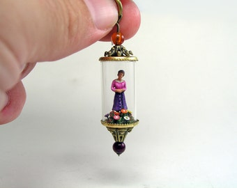 Miniature world. Woman standing in a garden of colorful flowers and bushes. Romantic pendant.