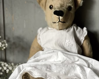 A wonderful 1960's Pedigree teddy bear in an antique cotton embroidered dress