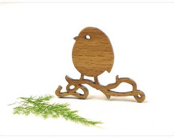 wooden brooch with majestic bird on a curved branch