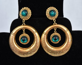 Vintage 1980s statement earrings in antiqued gold tone metal with emerald green plastic cabochons clip on