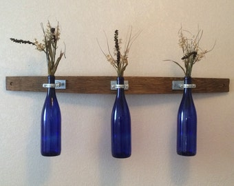 Wine bottle bud vases on wine barrel stave