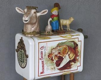 "Assemblage goat, ""On the Farm.""  Porcelain goat head, repro tin, industrial spools, brass decor, porcelain and chalkware farm figures."
