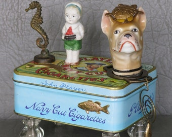 "One-of-a-kind sea-themed assemblage dog, ""Skipper.""  Porcelain dog head, cigarette tin body, knob feet, seahorse tail and aquatic decor."