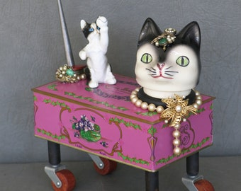 """Cat assemblage, """"Play Date.""""  Mother and daughter cats.  Louis Sherry chocolate tin, industrial bobbins, porcelain cats and jewelry."""