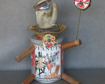 """One-of-a-kind assemblage elephant, """"Peanut.""""  Porcelain head, Planter's Peanuts tin body, bobbin legs, crystal and brass embellishments."""