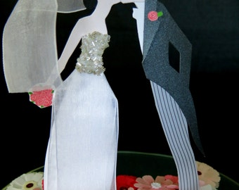 Wedding cake topper.  Contemporary style paper art with kissing Bride and Groom standing on mirror surrounded by pink flowers.
