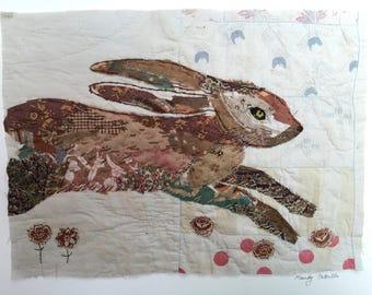 Unframed appliqued and hand embroidered hare on very old quilt fragment