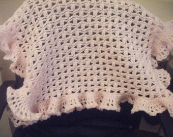 Lacy crochet baby blanket with ruffled edging.