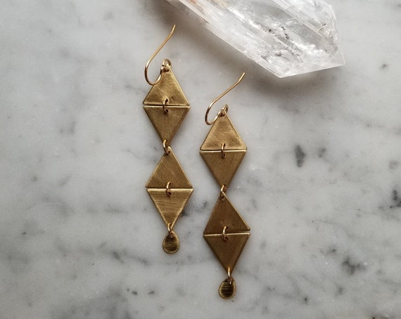 Geometric brass connected triangles with tiny brass teardrops