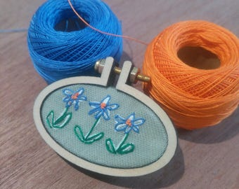 Hand embroidered brooch, mounted in a wooden, miniature embroidery hoop. Featuring blue flowers.