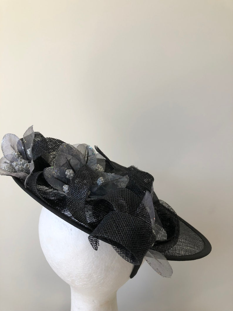New black saucer fascinator with silver flowers and black loops on a headband!