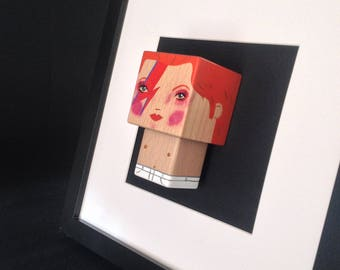 "Framed ""David Bowie Aladdin Sane"" figurine."