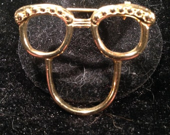 4776b140bf3 Gold glass holder pin in the shape of a pair of glasses with a funny face  designed by SCO Mfg s