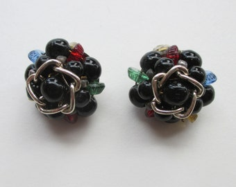 Vintage Beaded Clip-On Earrings. German manufactured midcentury black bead clusters with red, green and blue accents.