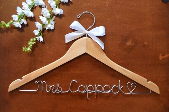 Personalisierte Draht Namen Kleiderbügel mit einer Schleife.