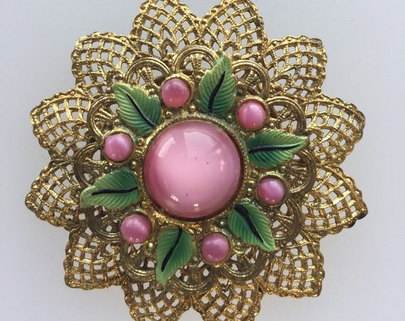 A striking Czechoslovakian filigree brooch set with pink glass and enamel