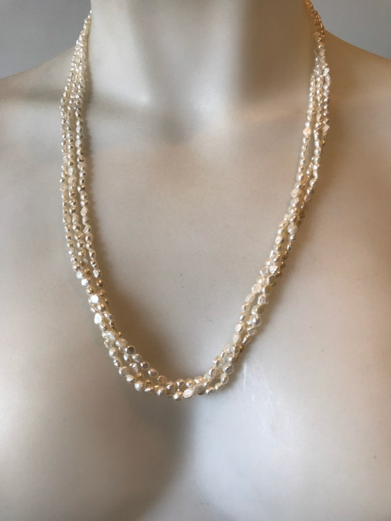 A striking  long length 24 inch vintage beaded 3 stranded creamy white cultured baroque rice pearl necklace