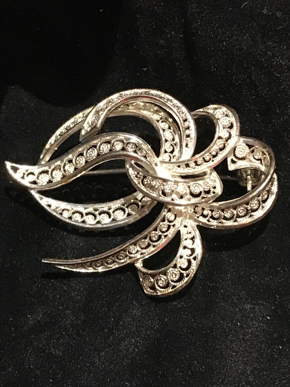 A beautiful vintage silver fine-filigree ribbon swirl  brooch