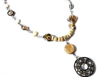 Necklace with beige and cream beads. Handcrafted sandy-colored beaded collar, mother-of-pearl, silver-colored pendant, metal shell pendant.