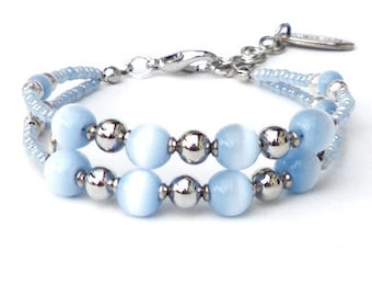 Blue bracelet with ice blue cat's eye beads and seed beads. Handcrafted wristband, silver-colored beads, dividers, tiger eye beads, 2 strand