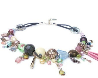 Necklace with ceramic beads and glass beads in pastel shades and silver-colored beads. Handcrafted choker with charms, grey faux suede cords