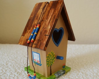 Hand painted beige house with blue shutters and windows, wood roof and flowers, ivy and a tree, wooden house