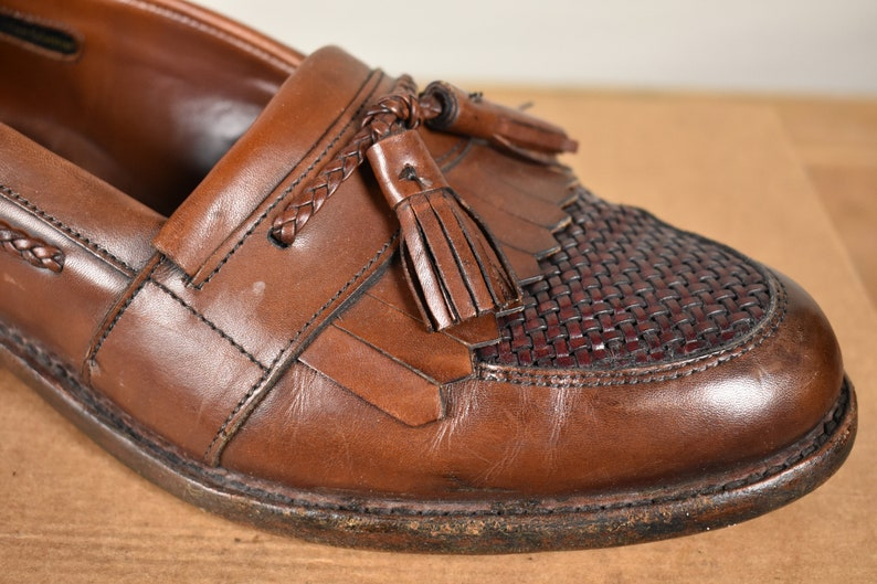 b982bed08a41f Allen Edmonds Cody Brown Moc Toe Kiltie Tassel Loafer W/ Woven Plug And  Braided Lacing Size: 8.5D