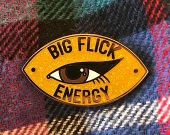 Big Flick Energy yellow glitter hard enamel pin with brown eye