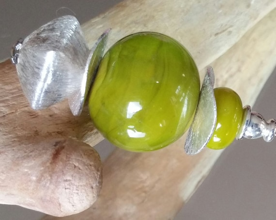 "Fibula bead in the ""Olive"" green light"