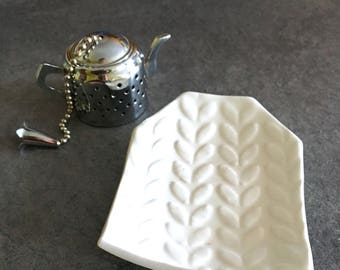 White saucer shaped tea bag made from handmade clay with imprinted small regular leaves