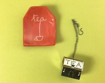 Red Saucer shaped tea bag made of handmade clay with drawn the word tea