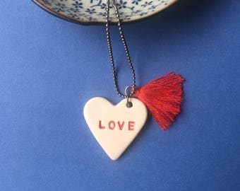 Long necklace with Tiffany chain with tassel and white heart shaped clay pendant with engraved the inscription LOVE