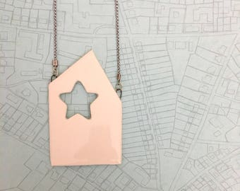 Necklace made of chain with a house shaped pendant with star windows