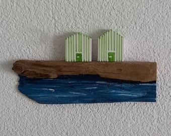 maritime beach houses with green stripes, driftwood as beach & sea