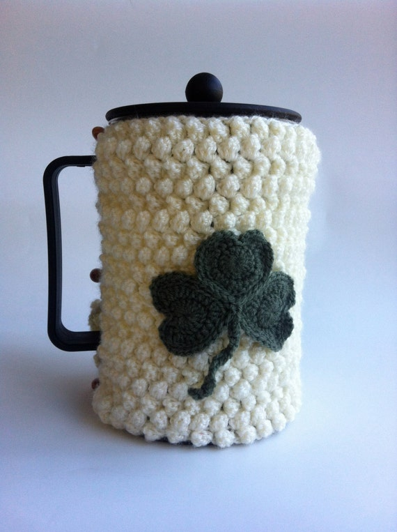Crochet Cream Coffee Cozy with sage green Shamrock detail, duffle pegs to close