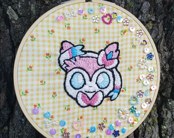 Sylveon Handmade Embroidery Hoop with Sequins on yellow gingham fabric