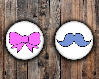 Gender reveal pins.  Blue mustache and Pink bow.