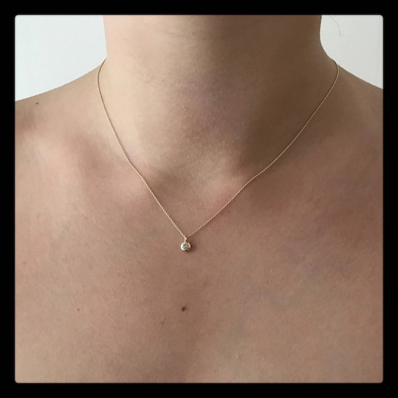A .03ct diamond set in 14k gold on a 42cm solid gold chain.
