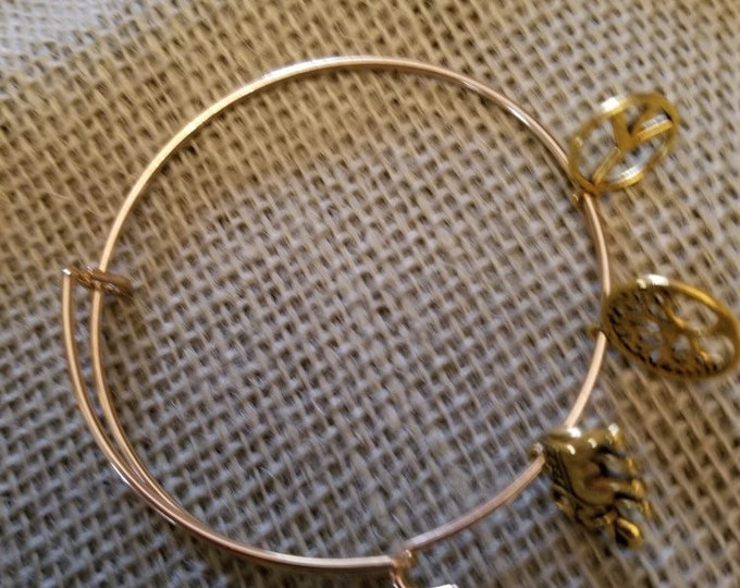 Gold colored charm bracelet with Peace sign, Tree of Life , Elephant