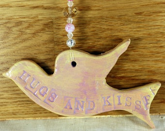 Flying Bird, Hugs and Kisses, Hanging Decoration, with nice pale pink and lilac glaze in a lovely white gossamer bag. Great for Mothers Day.