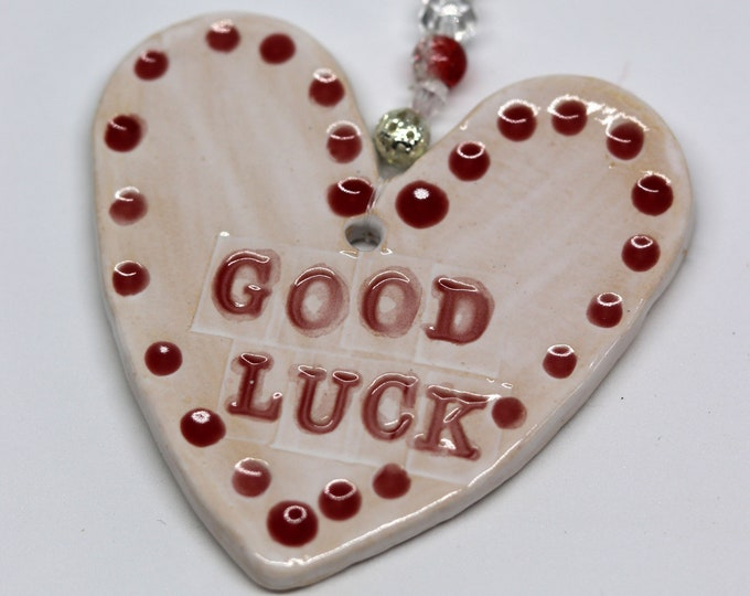 Good Luck Handmade Pottery Heart with red & white glazes. Sent to you in a gossamer bag ready to give as a gift.