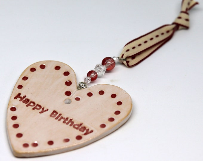 Happy Birthday Pottery Heart, Hand Painted with red and white glazes and sent to you in a gossamer bag ready to be given as a gift.