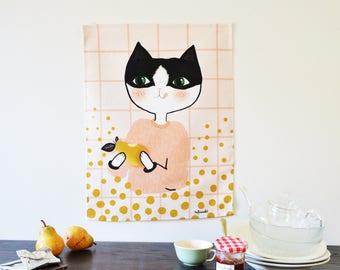 Torchon chat noir et blanc qui mange une poire. illustration impriméesur fond à carreaux roses sur fond blanc. lin/coton - 42cm X 55 cm.