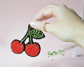 Broche cerises brodée à la main de perles de rocailles rouges sur  feutrine noire. Bijou fruit brodé.